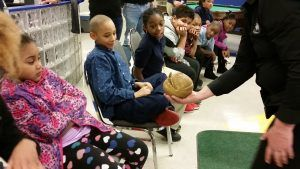 A Wildlife Defender showing a balled up armadillo to students.