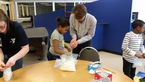 Paul Brooks, a professor in the Department of Anesthesiology, helps a student make ice cream in a bag to show how the addition of salt lowers the freezing point of water.